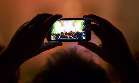 A fan watches a gig through his mobile phone