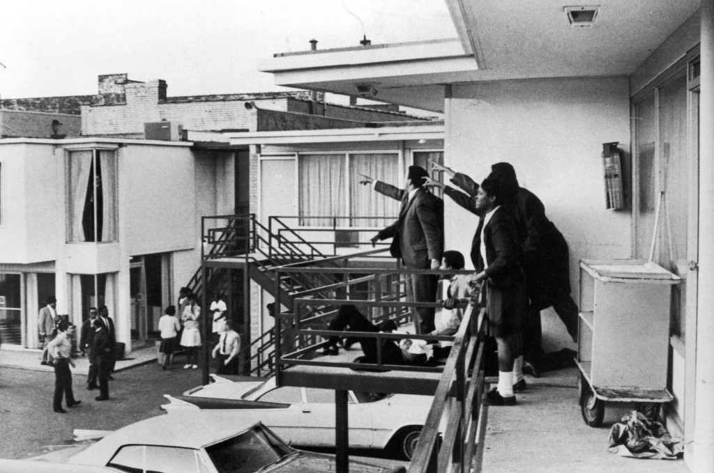 Civil rights ldr. Andrew Young (L) and others standing on balcony of Lorraine motel pointing in direction of assailant after assassination of civil rights ldr. Dr. Martin Luther King, Jr., who is lying at their feet.