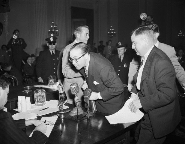 "28 Oct 1947, Washington, DC, USA --- Screenwriter Dalton Trumbo, one of the ""Hollywood Ten"" targeted by the Un-American Activities Committee, leaves the witness stand shouting ""This is the beginning of Amercan concentration camp."" He is the second Hollywood personality in two days to defy investigators questions regarding Communist affiliation. He is accompanied by his defense lawyers Robert Kenny and Bartley Crum. --- Image by © Bettmann/CORBIS"